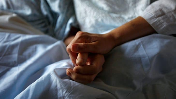 A woman holds the hand of her mother who is dying from cancer during her final hours at a palliative care hospital in Winnipeg July 24, 2010. Picture taken July 24, 2010. REUTERS/Shaun Best (CANADA - Tags: HEALTH) - RTR2ID7P